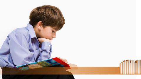 Ein kleiner Junge, der sitzt und aufmerksam ein Buch liest