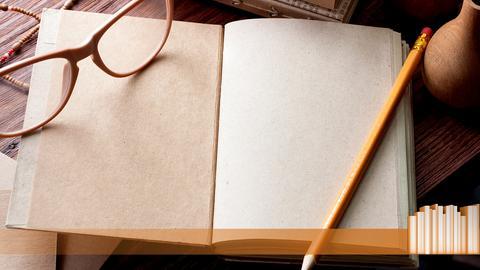 Ein geöffnetes Buch mit leeren Seiten, einem Stift und einer Brille.