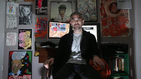 Künstler Michael DeForge sitzt vor einem Schreibtisch mit PC, an der Wand hinter ihm hängen seine Zeichnungen