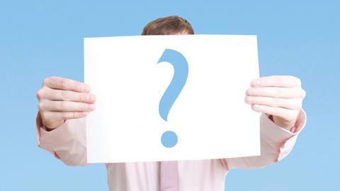 Ein Mann hält ein Plakat mit einem Fragezeichen hoch.