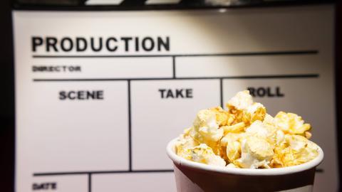 Eine Filmklappe im Vordergrund ein Becher mit Popcorn