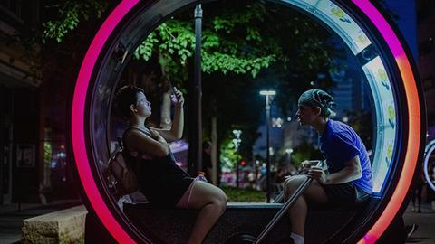 """Ein Zylinder der Kunstinstallation """"Loop"""": Zwei Menschen sitzen in dem Objekt."""