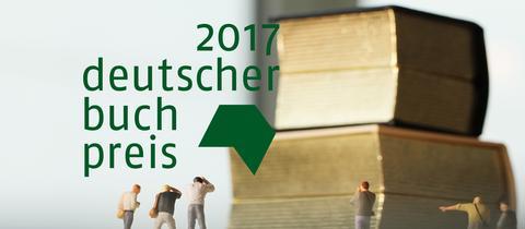 Spielfiguren haben Bücher im Blick - daneben das Logo des Deutschen Buchpreises 2017