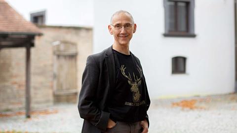 Michael Lemster steht vor Gebäuden und lächelt in die Kamera.