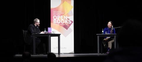 Ein Mann und eine Frau sitzen auf einer Bühne an Tischen mit Mikro und Wassergläsern. Daneben ein Aufsteller mit dem Logo von Open Books 2020.