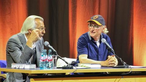 Otto und Bernd Eilert sitzen auf Bühne am Tisch