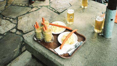 Gläser mit Erbsensuppe, in denen Bockwürstchen stecken, und Biergläser auf einem Betonklotz.
