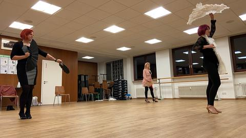 Drei Frauen tanzen in einem Saal mit Fächern in der Hand