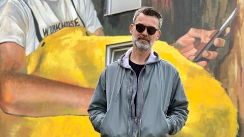 Streetart-Künstler Case Ma'Claim in Bad Vilbel, Mann mit Brille; Jeans und Jacke vor einem Graffiti