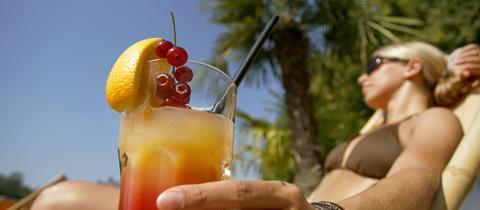 Eine Frau in einem Liegestuhl hält einen Cocktail in der Hand.
