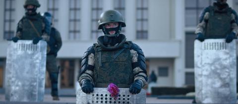 Soldaten vor dem belarussischen Parlamentsgebäuse. Demonstranten haben ihm eine rote Blume ans Abwehrschild gesteckt.