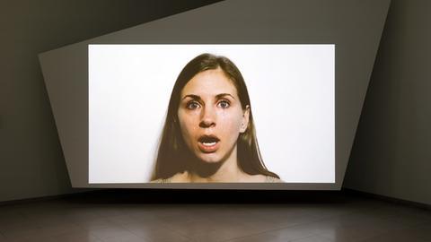 Ein Monitor zeigt einen junge Frau mit Tränen im Gesicht
