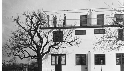 Ein Schwarz-Weiß-Bild zeigt zwei Frauen auf einer Dachterrasse. Eine von ihnen hält ein Kind auf dem Arm. Vor dem Haus ist ein kahler Baum zu sehen.