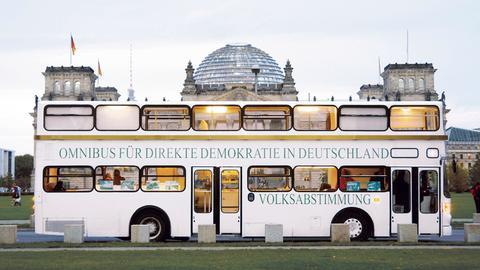 """Bus mit der Aufschrift """"Omnibus für Direkte Demokratie in Deutschland"""" parkt vor dem Reichstag in Berlin"""
