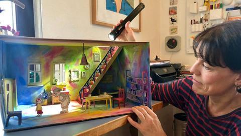 Illustratorin Antje Damm leuchtet mit einer Taschenlampe ihre Pappkulisse aus