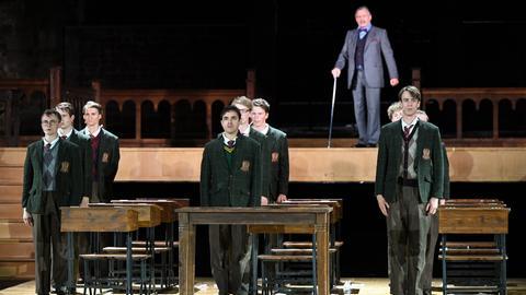 """Eine Szene der Stücks """"Der Club der toten Dichter"""". Im Vordergrund Schüler, die in Reih und Glied, ordentlich und voller Angst neben ihren Tischen stehen. Im Hintergrund ein Lehrer mit einem Stock."""