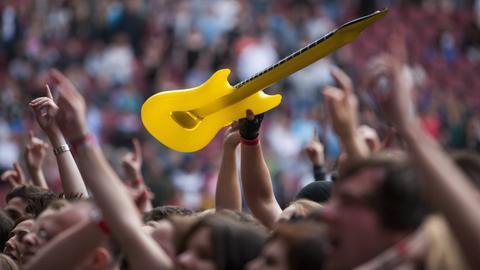 Publikum bei einem Ärzte-Konzert, einer hält eine Plastik-E-Gitarre hoch