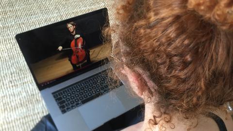Eine Frau schaut ein Chello-Konzert im Livestream an.
