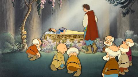 Szene aus Disneys Schneewittchen - Schneewittchen liegt im Sarg, der Prinz steht davor, die Zwerge im Halbkreis drum herum