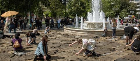 Bei einer Kunst-Performance auf dem Athener Syntagma-Platz nähen junge Menschen Jute-Säcke zusammen.