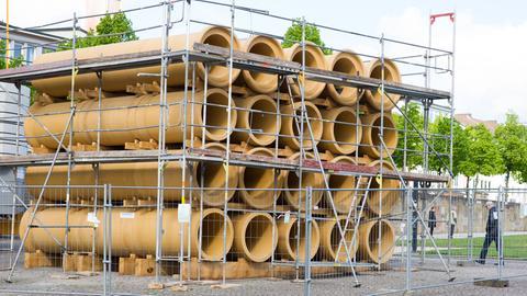 Röhren vom documenta-Kunstwerk von Hiwa K. umgeben von einem Baugerüst und einem Bauzaun.