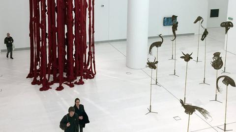 Adam Szymczyk, der künstlerische Leiter der documenta, geht unter einem Kunstwerk von Cecilia Vicuna entlang