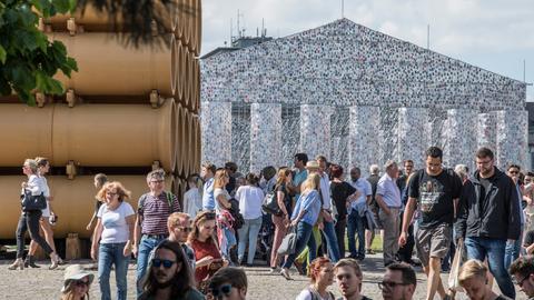 """Besucher vor der Röhren-Installation von Hiwa K. (l) und dem """"Parthenon of books"""" der argentinischen Künstlerin M. Minujin."""