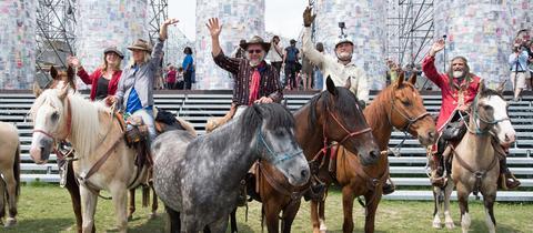 """Reiter vom """"The Athens-Kassel Ride"""" des Künstlers Ross Birrell stehen am mit ihren Pferden in Kassel vor dem Nachbau des Parthenon-Tempels."""