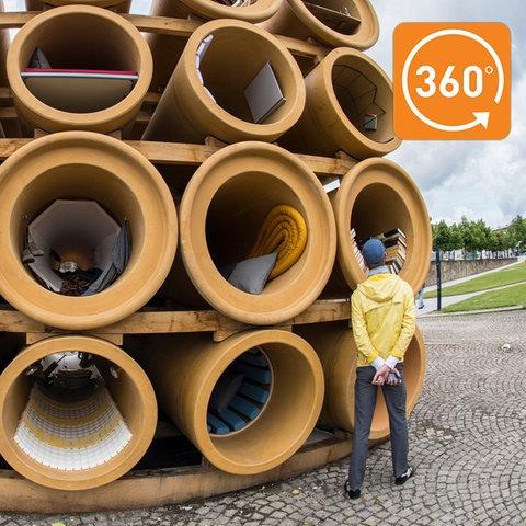 """Aus übereinandergestapelten Kanalisationsröhren, die """"wohnlich eingerichtet sind"""", besteht das Werk des Künstlers Hiwa K."""