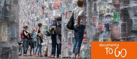 """Besucher betrachten auf der documenta in Kassel den """"Parthenon of Books"""" von Marta Minujin."""