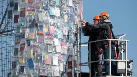 """In Plastik eingehüllte Bücher werden am Stahlgerüst des documenta-Kunstwerks """"The Parthenon of Books"""" in Kassel angebracht."""