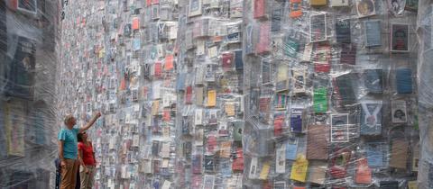 """Besucher der documenta betrachten den """"Parthenon of Books"""""""