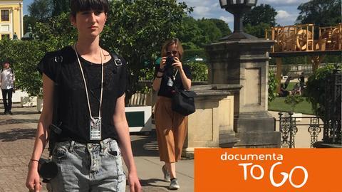 Eine documenta-Mitarbeiterin trägt vor der Orangerie einen mobilen Lautsprecher aus dem das Flüsterwerk von Pope.L säuselt