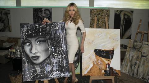 Die Unternehmerin und ehemalige Porno-Darstellerin Dolly Buster malt gerne erotische Kunst. Hier ist sie mit zweien ihrer Werke zu sehen.
