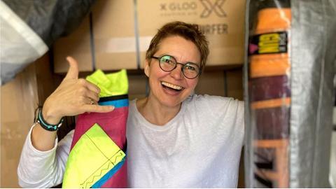 Doris Ivanschitz - aus alten Segeln stellt sie Kleidung und Rucksäcke her. Kurzhaarige Frau mit Brille - lachend - mit Surfergruß - im Arm ein zusammengerolltes Segel.