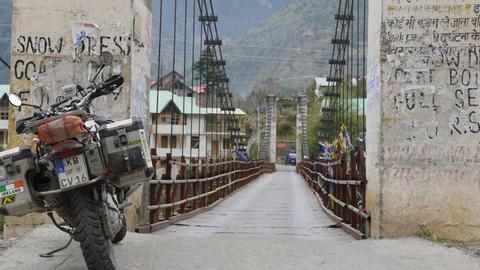 Motorrad steht neben Hängebrücke