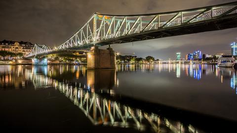 Der Eiserne Steg in Frankfurt spiegelt sich im dahinfließenden Wasser