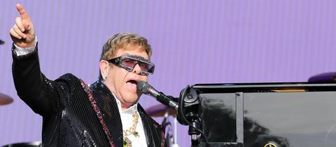 Elton John singt am Klavier