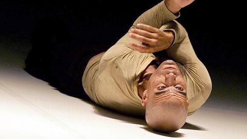 Choreograph Emanuel Gat liegt auf dem Rücken auf einem weißen Boden. Er trägt ein beigefarbenes Longsleeve und eine schwarze Hose. Er streckt seine Arme in die Luft und überkreuzt sie dabei.