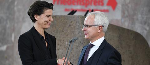 Carolin Emcke erhält den Friedenspreis aus den Händen von Heinrich Riethmüller, dem Vorsitzenden des Börsenvereins des Deutschen Buchhandels.