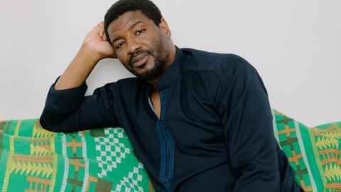 Portrait von Emeka Ogboh, wie er auf einem Sofa sitzt.