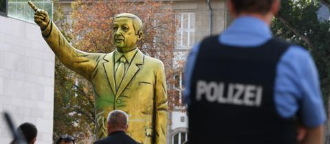 Passanten und Polizei stehen auf dem Platz der Deutschen Einheit vor einer goldenen Erdogan-Statue.