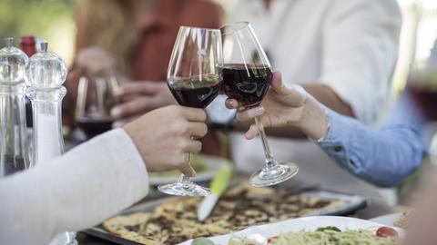 Menschen am einem gedeckten Tisch prosten sich mit Rotwein zu.