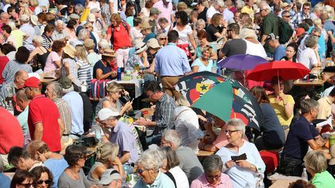 Die Plätze vor der Bühne waren schnell weg. Viele hatten sich neben Klappstühlen und Decken auch Schirme als Schutz vor der Sonne mitgebracht.