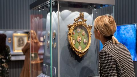 Besucherin vor einer Vitrine betrachtet Portrait-Miniaturen