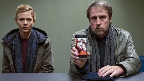 Eine Polizistin und ein Polizist zeigen in einem Verhörraum ein Handyfoto eines Kindes.