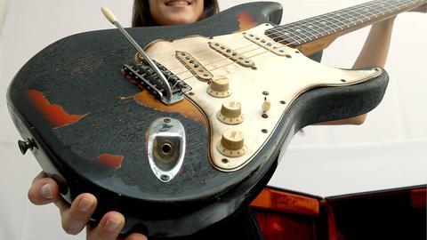 Zu sehen ist eine sehr benutzte, historische braune Stratocaster-Gitarre - auf dieser Gitarre hat früher Jimi Hendrix gespielt