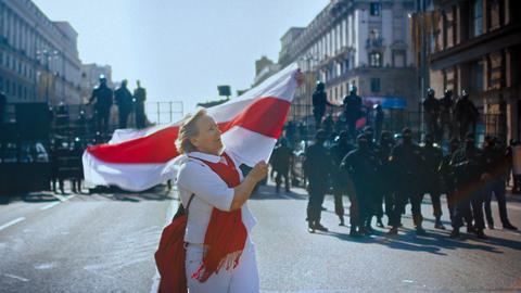 Eine Demonstrantin vor massiven Absperrung der belarussischen Spezialeinheiten.