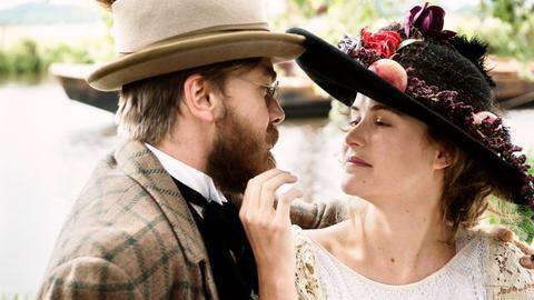 Ein Paar in Kleidung aus der Jahrhundertwende schaut sich verliebt an.