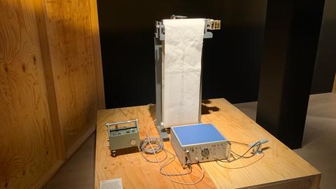 Ein Seismograf steht auf einem Holzpodest und schreibt Linien auf ein Blatt Papier.